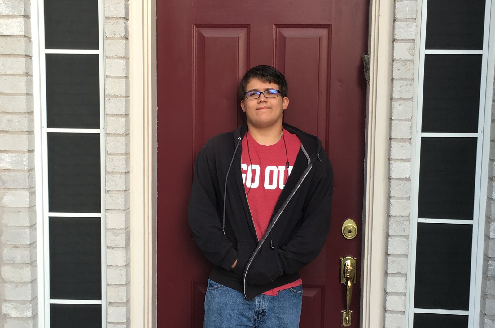 Son in front of door wearing GO OU shirt