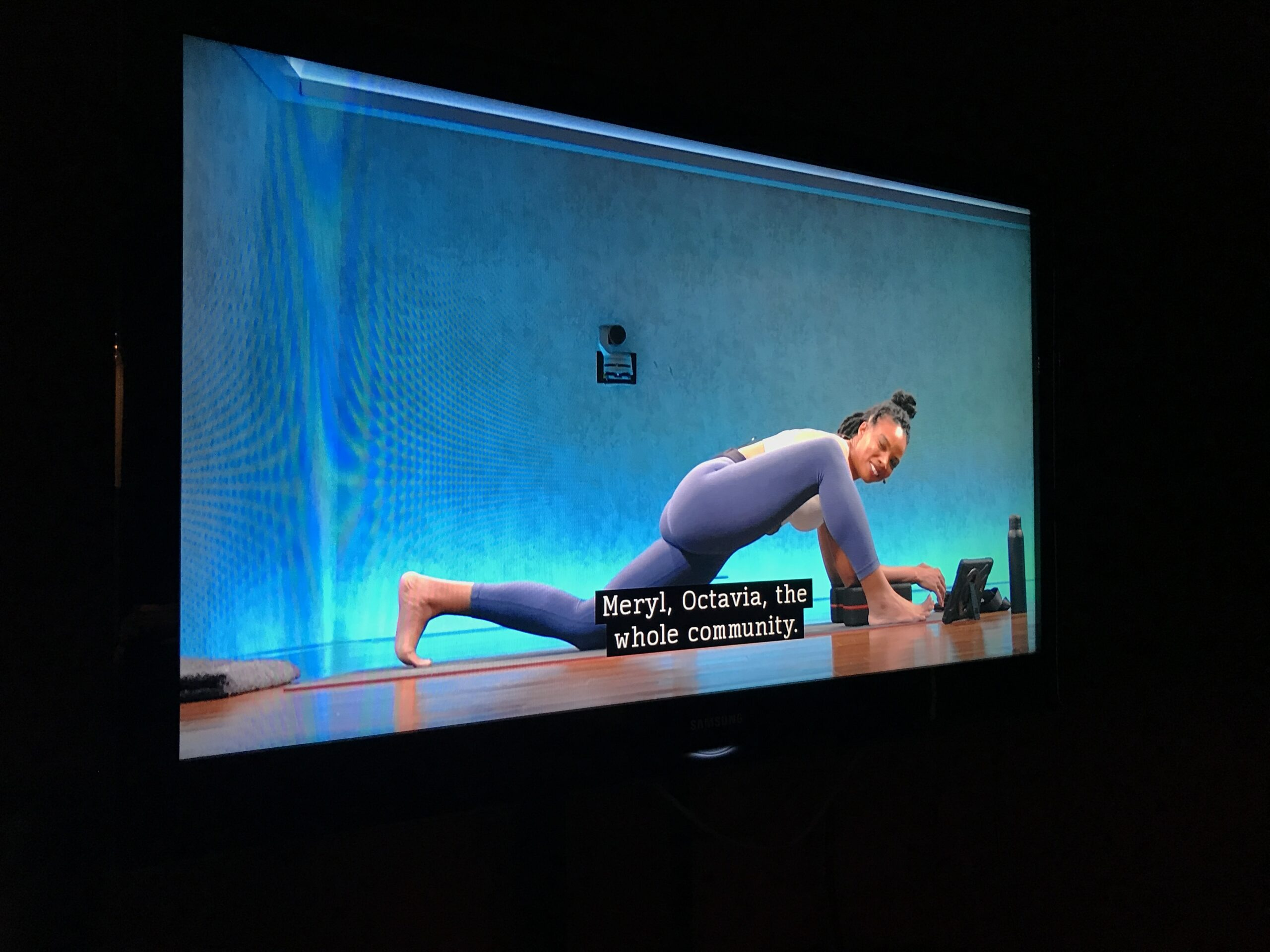 Woman in lizard pose in captioned Peloton workout video