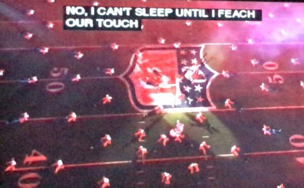 """Football field filled with dancers and captions show """"No, I can't sleep until I feach our touch."""""""